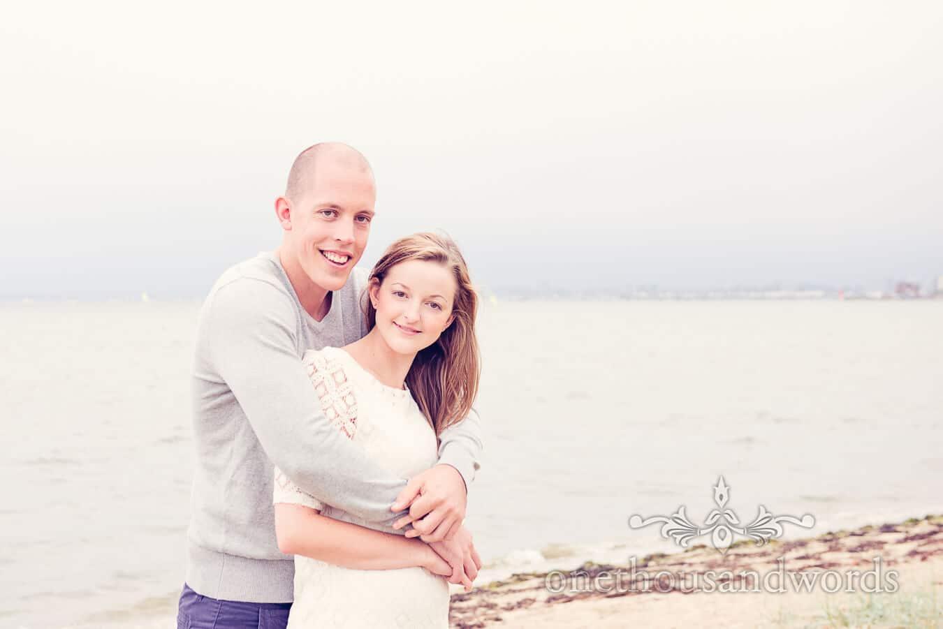 Bride and groom to be hug against seaside in Poole Harbour
