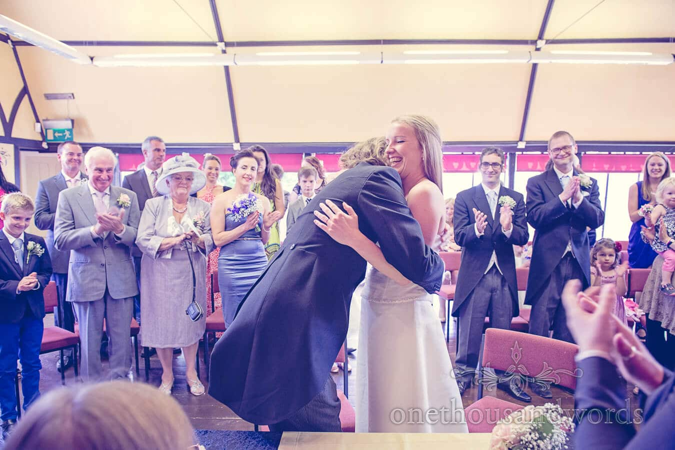Bride and groom hug at Tenbury Wells Pump Rooms wedding ceremony