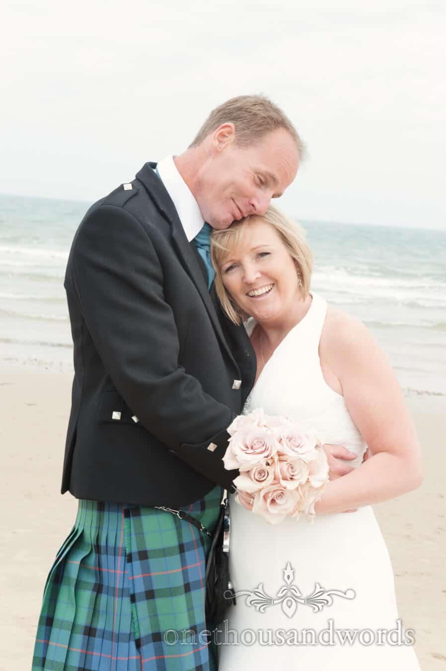 Bride and groom hug on Sandbanks Hotel Beach