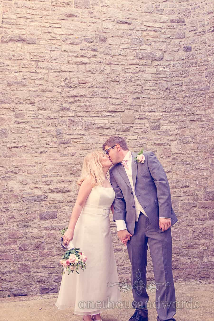 Bride and groom kiss against stone wall at Vintage Style Wedding