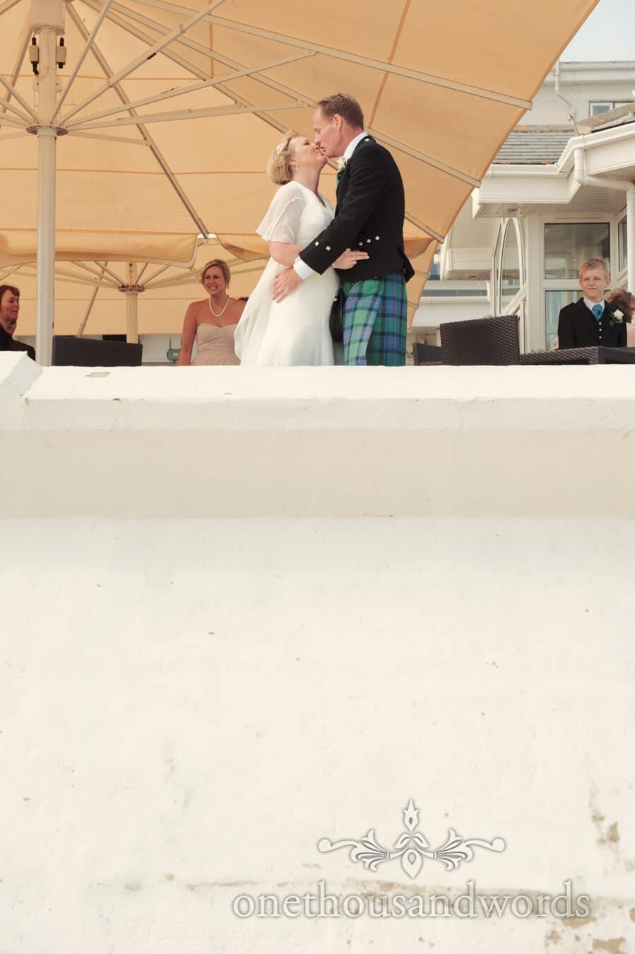 Bride and groom kiss by the sea at Sandbanks Hotel Wedding