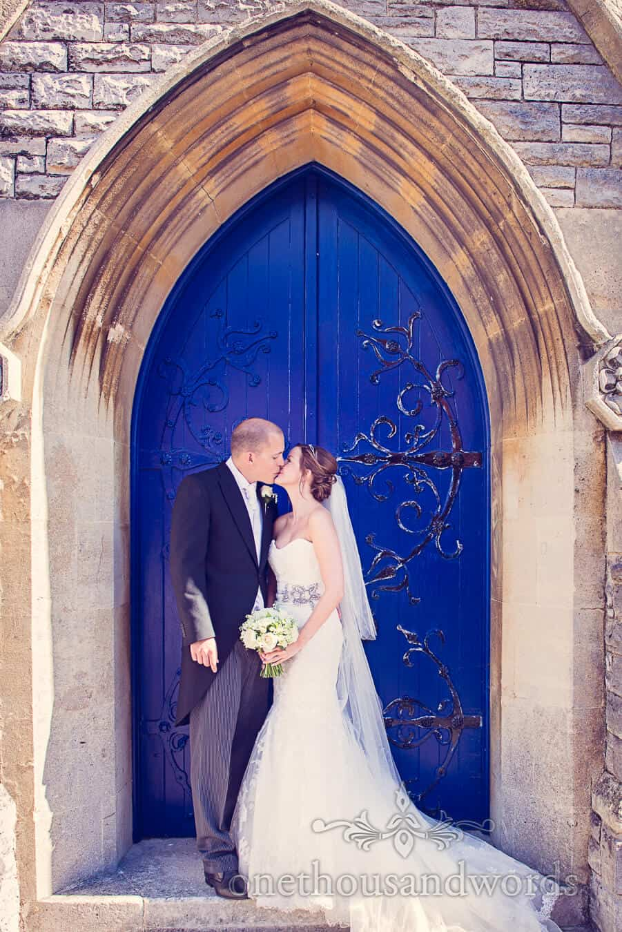 Bride and groom kiss in blue arch church doorway
