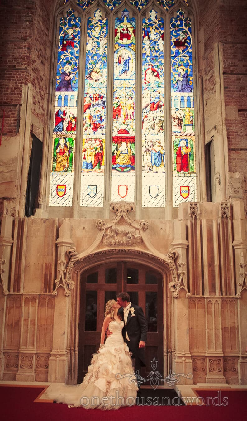 Bride and groom kiss under stained glass windows at Highcliffe Castle Wedding