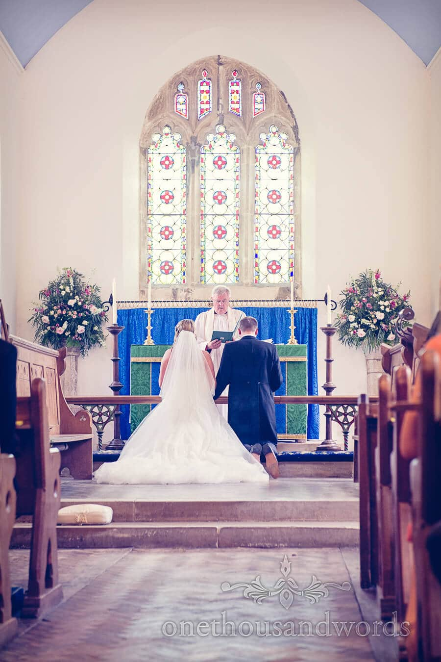 Bride and groom kneel before altar at church wedding ceremony