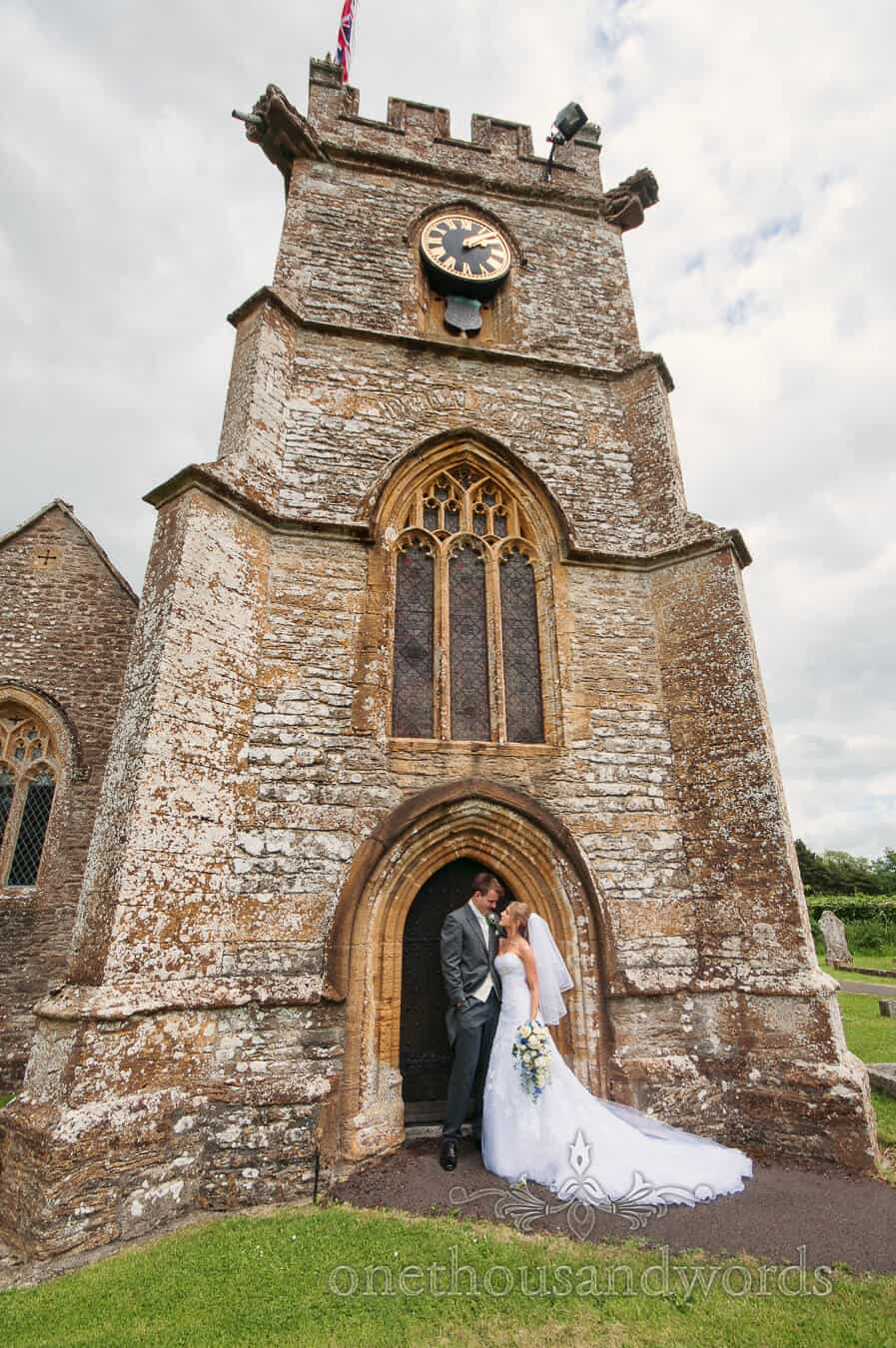 Bride and groom outside english country church wedding ceremony