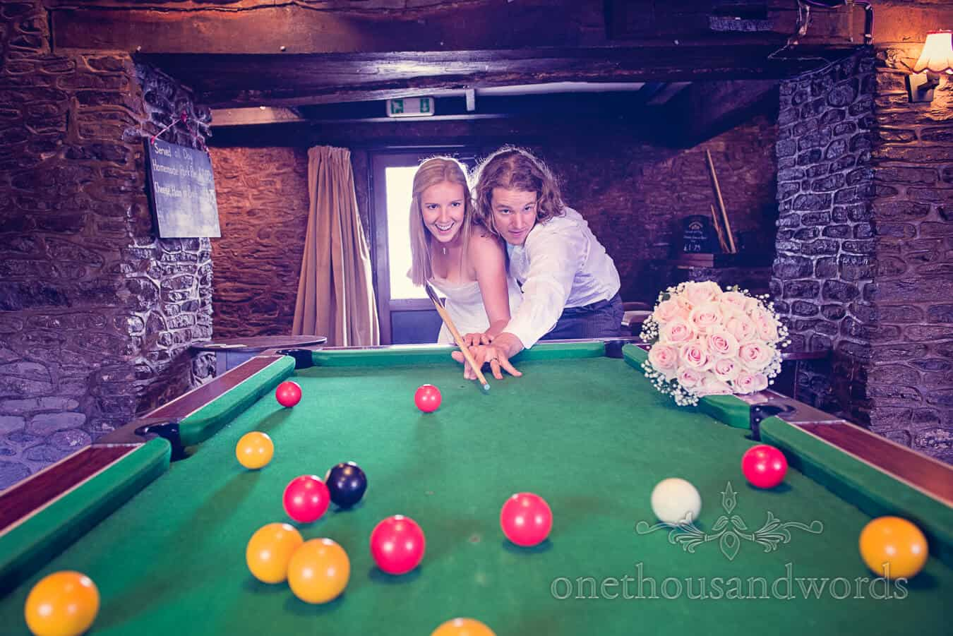 Bride and groom play pool at countryside pub on wedding day
