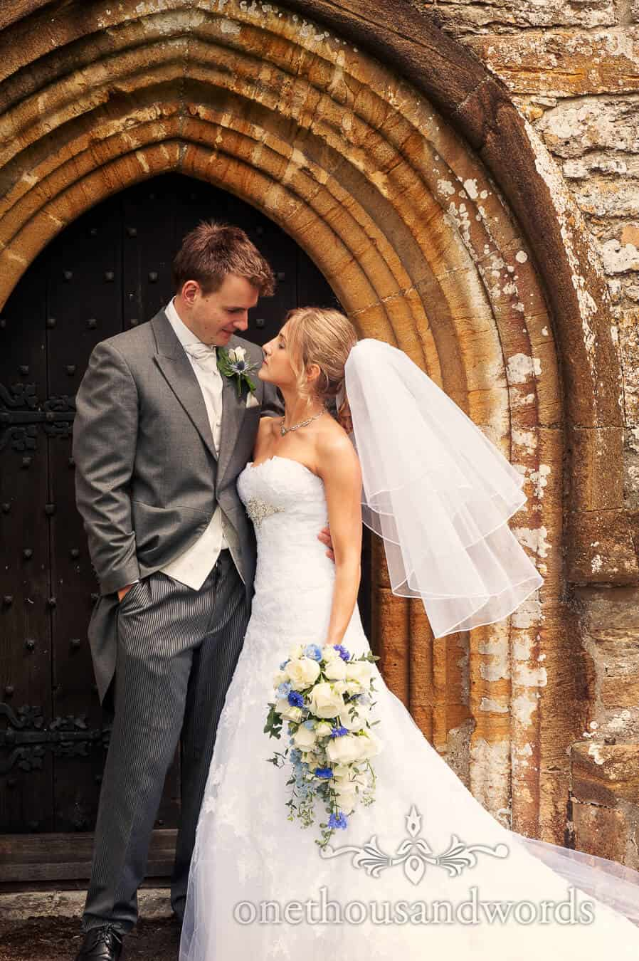 Bride and groom portrait outside country church doorway