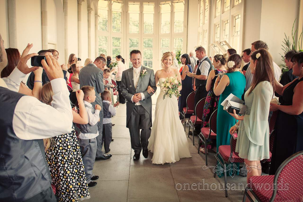 Bride and Groom walk down the aisle at Highcliffe Castle