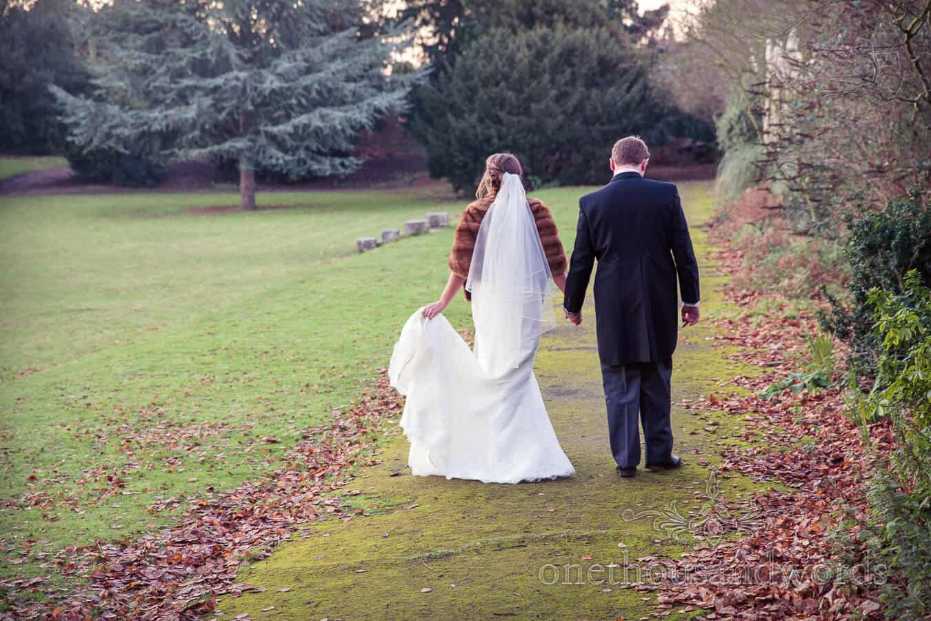 Bride and groom walk hand in hand at Hampton Court House Wedding