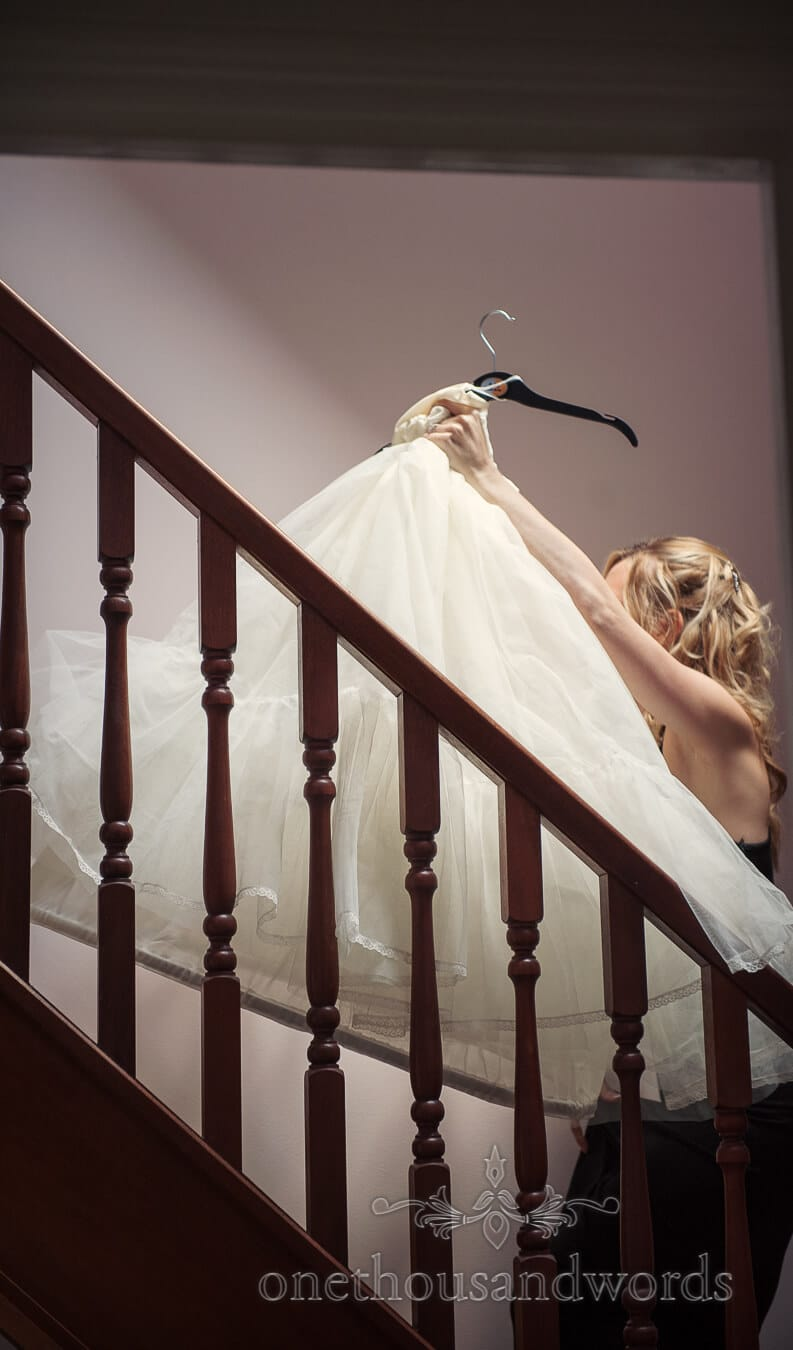 Bride carries Ian Stuart wedding dress netting up a staircase