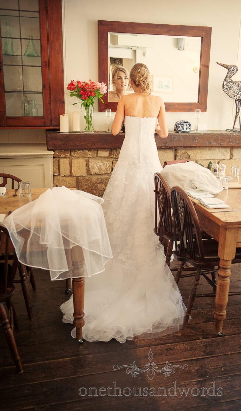 Bride checks wedding makeup in mirror at Country Theme Wedding