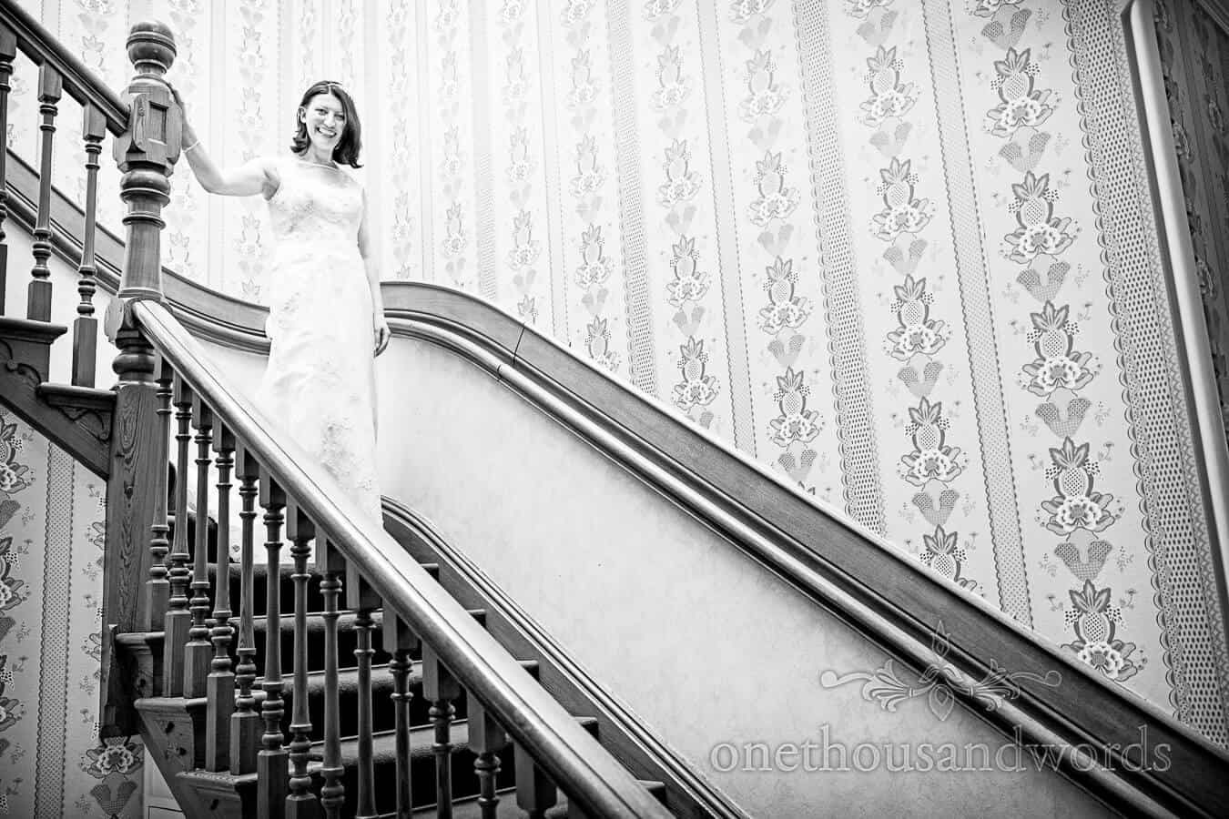 Black and White wedding photograph of Bride decending staircase