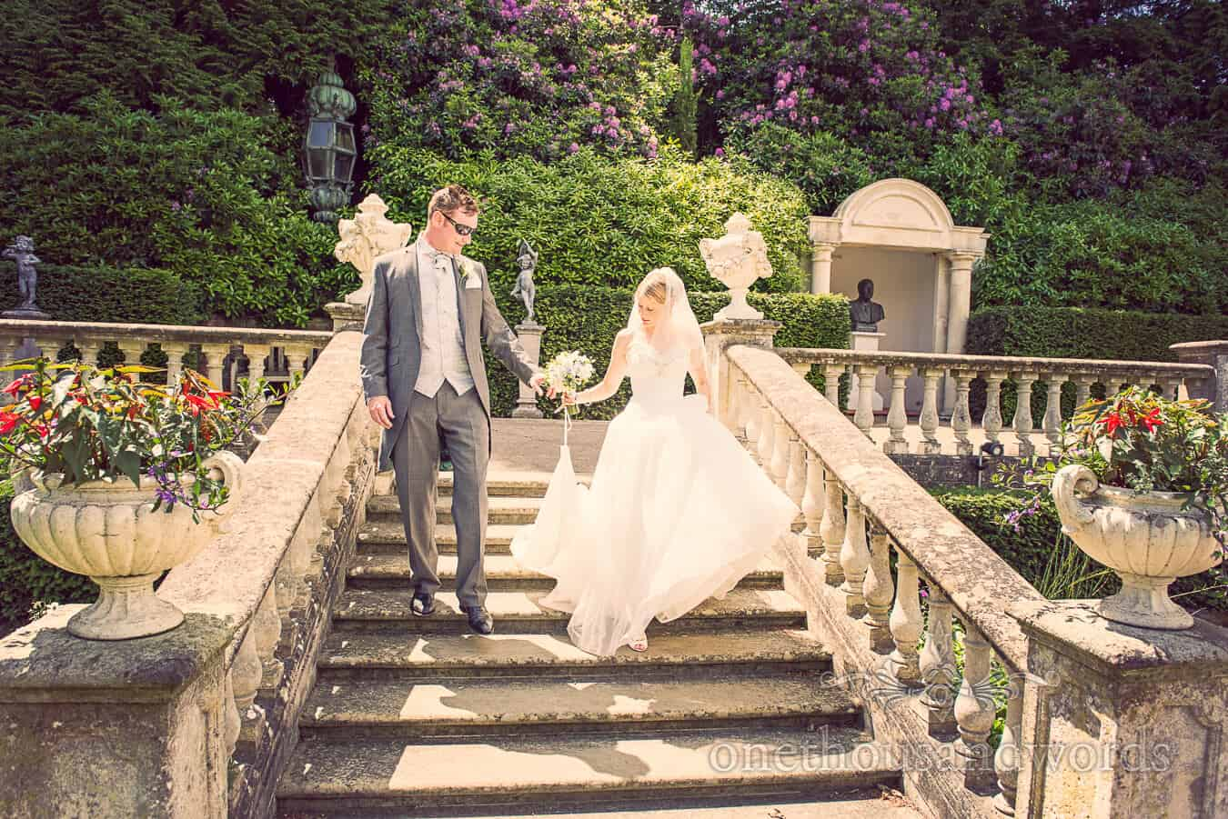 Bride and groom on stone stair case at Italian Villa Wedding venue in Dorset