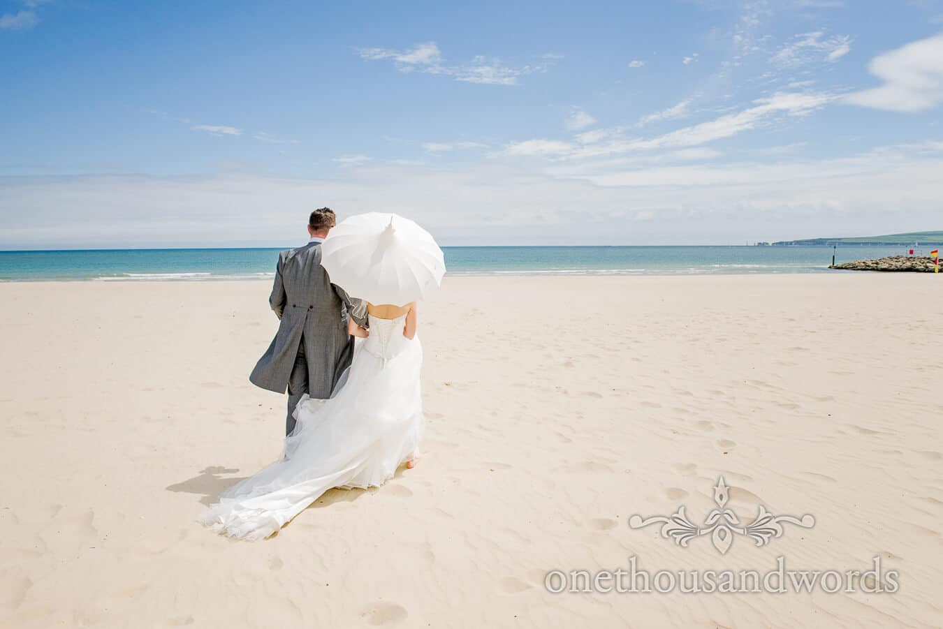 Bride and groom on white sand beach at Sandbanks Beach summer sun