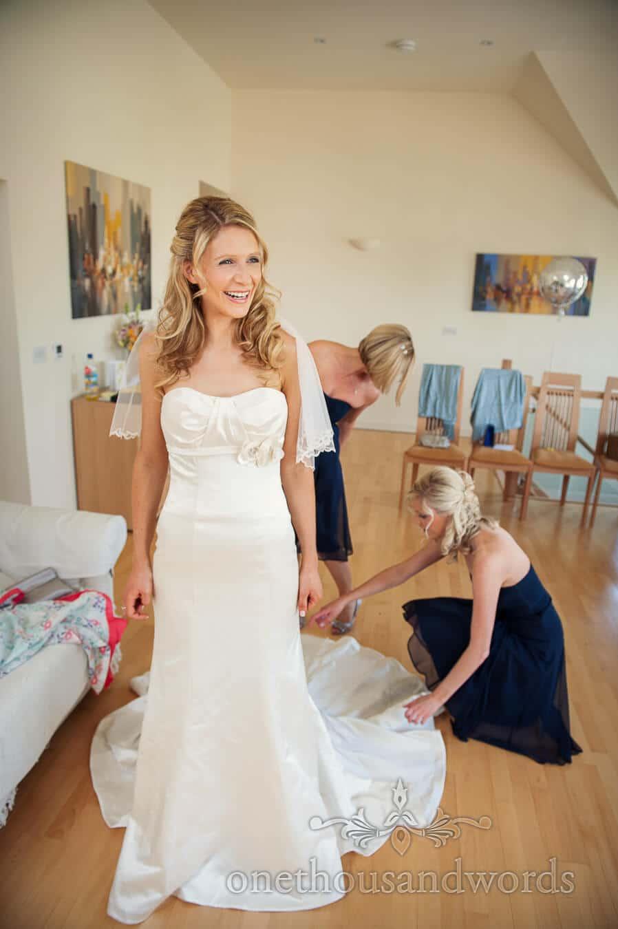 Bride has trumpet wedding dress adjusted by bridesmaids
