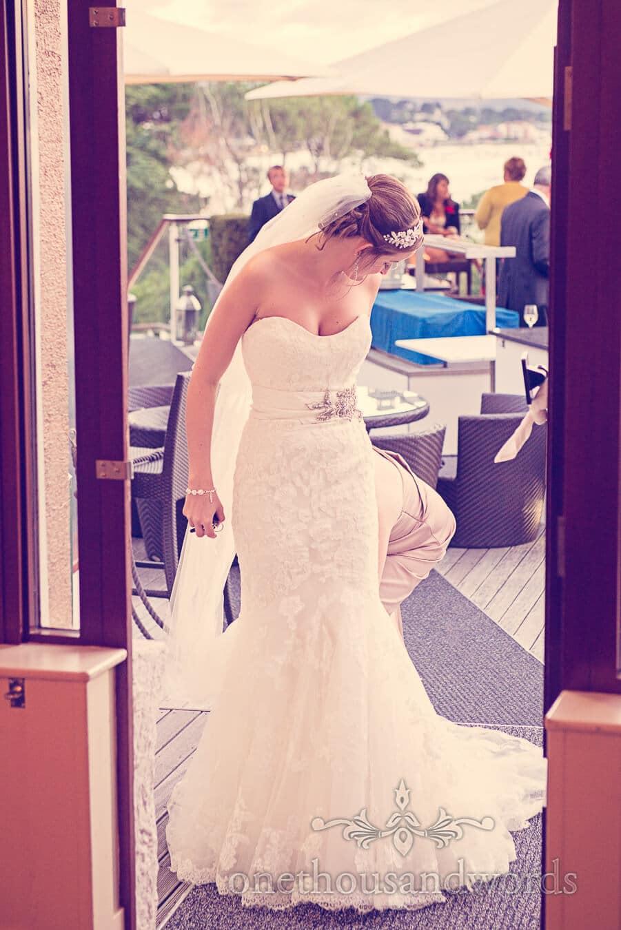 Bride has white wedding dress adjusted at Poole wedding venue