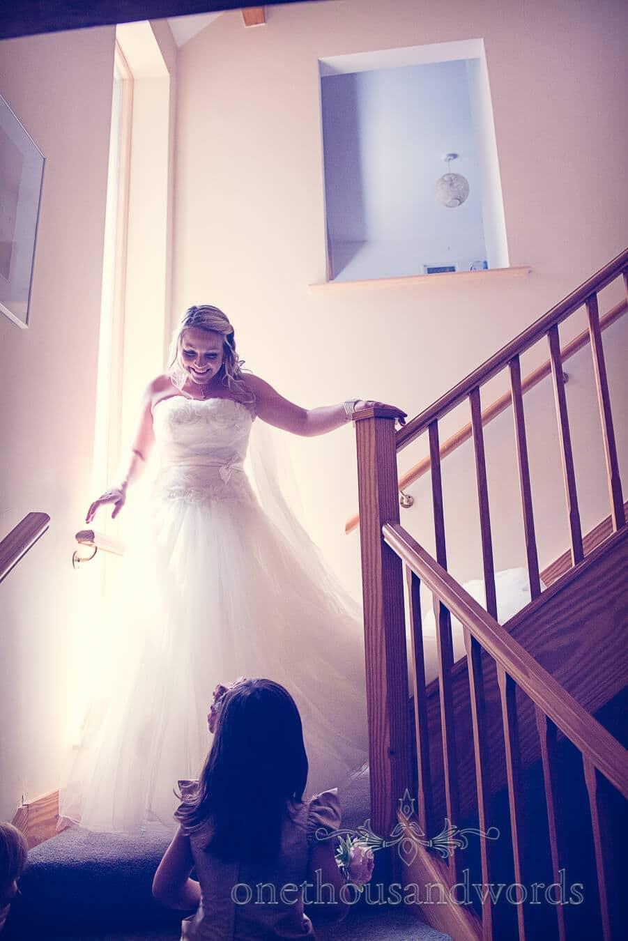 Bride in wedding dress decends stairs at Dorset Home Wedding