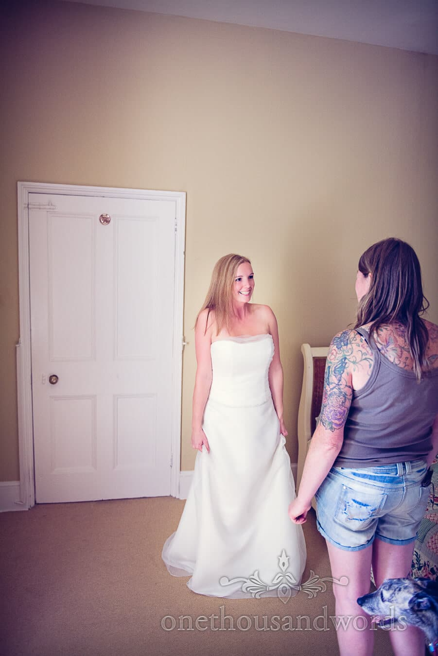 Bride in white wedding dress excited to see her friend on wedding morning
