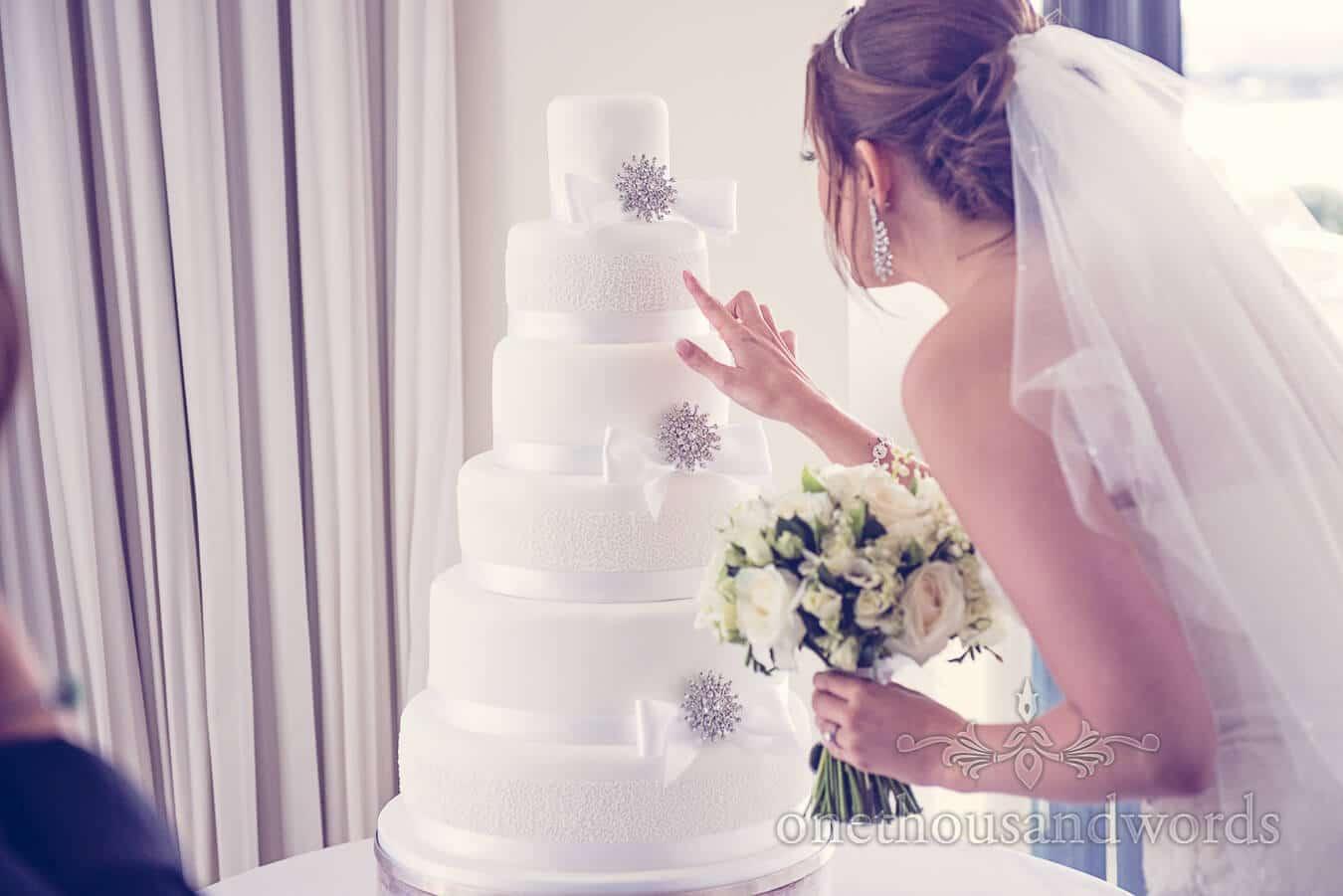 Bride inspects white wedding cake at Poole wedding venue