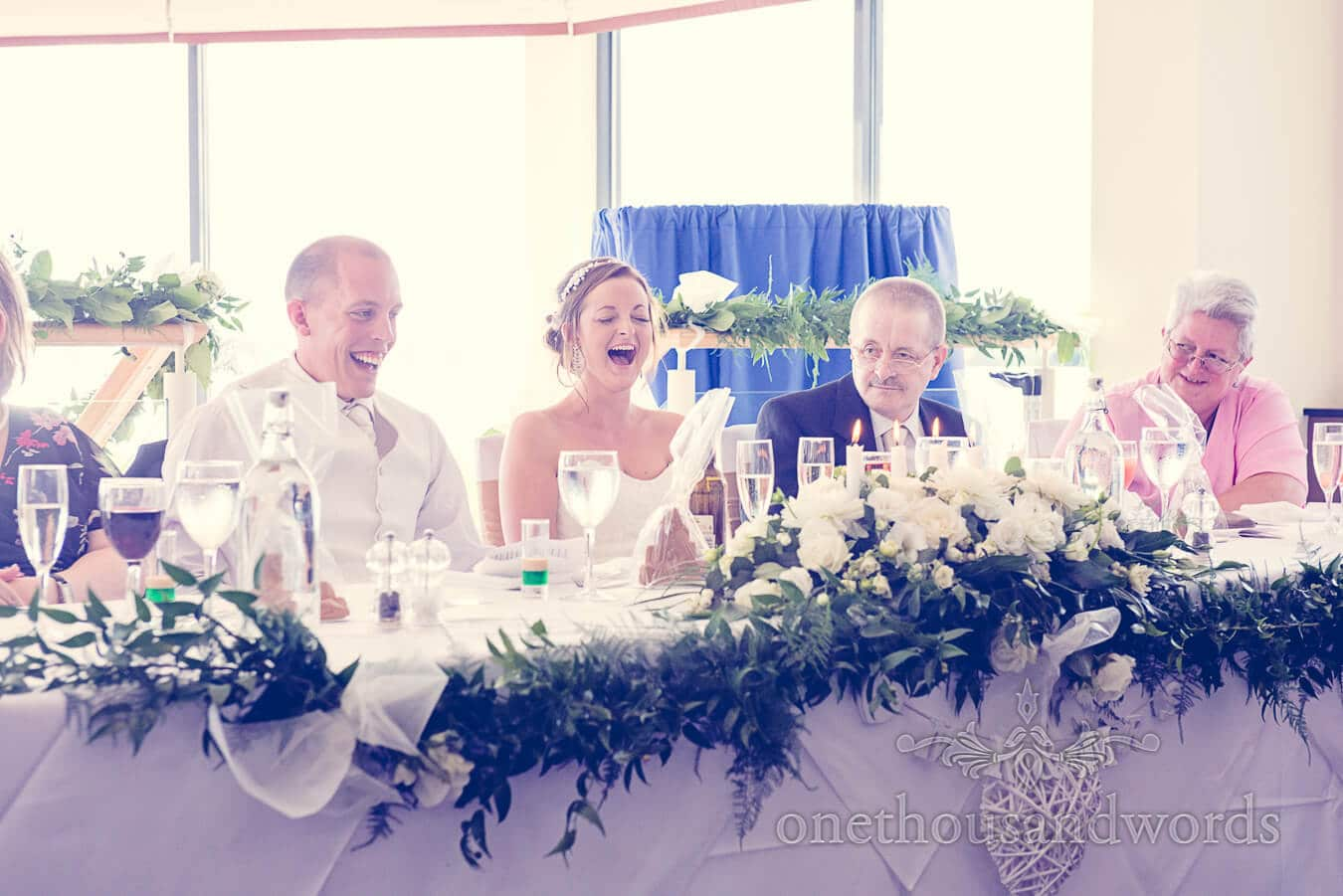 Bride laughs at wedding speeches at Harbour Heights Poole wedding venue