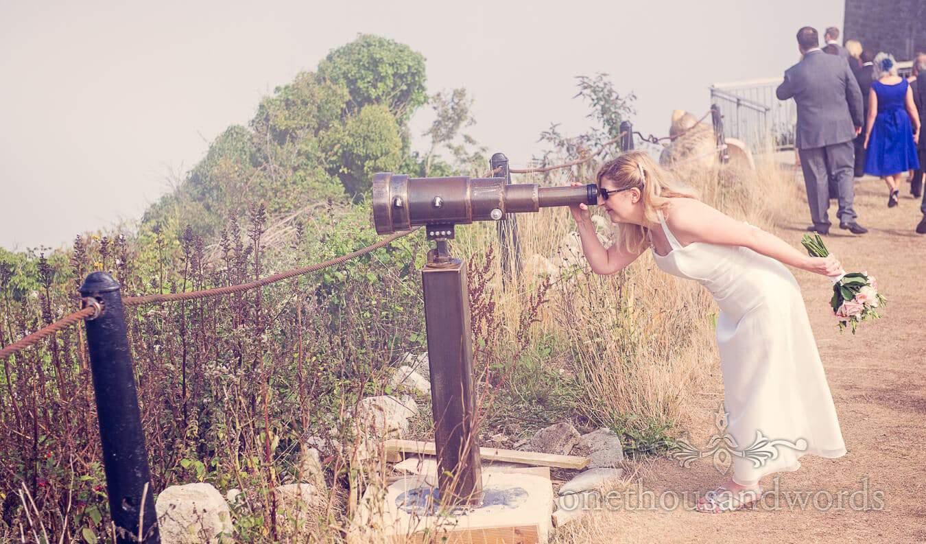 Bride looks through giant telescope at Durlston Castle Wedding