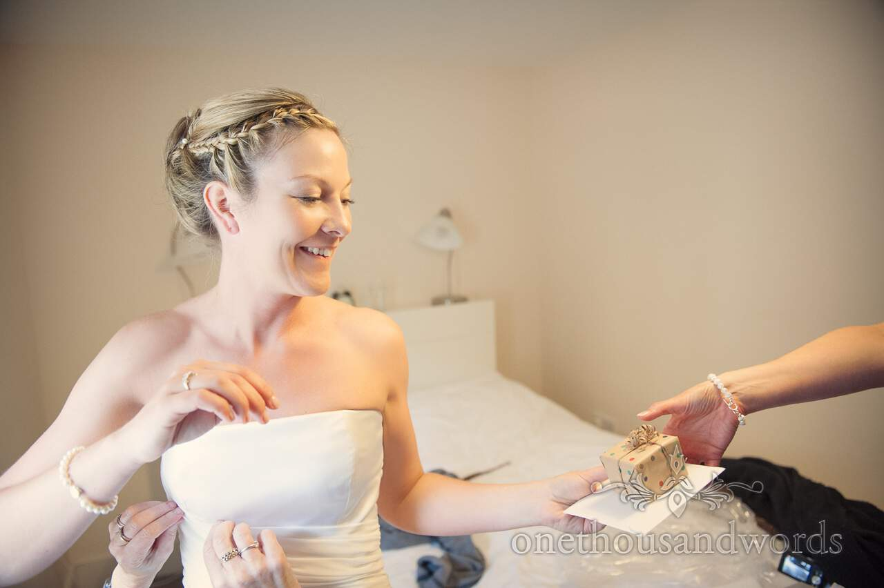Bride recieves gift whilst being dressed on wedding morning