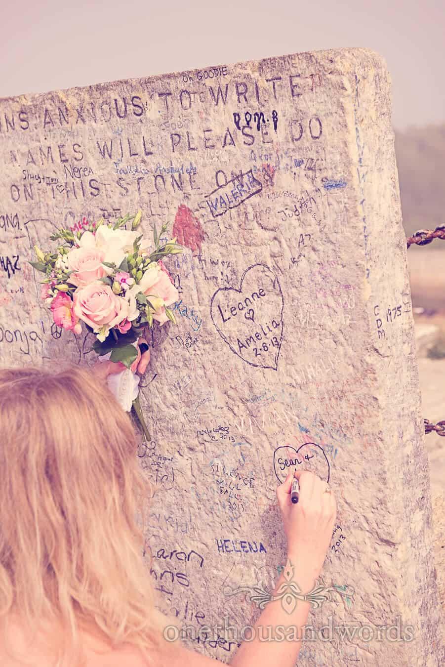 Bride signs graffiti stone at Durlston Castle Wedding venue