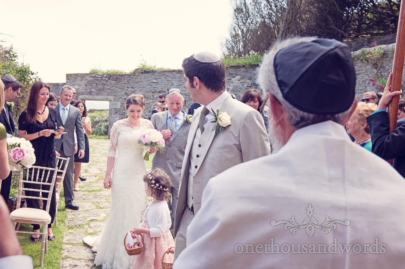 Bride walks down the aisle at outdoor Jewish wedding ceremony