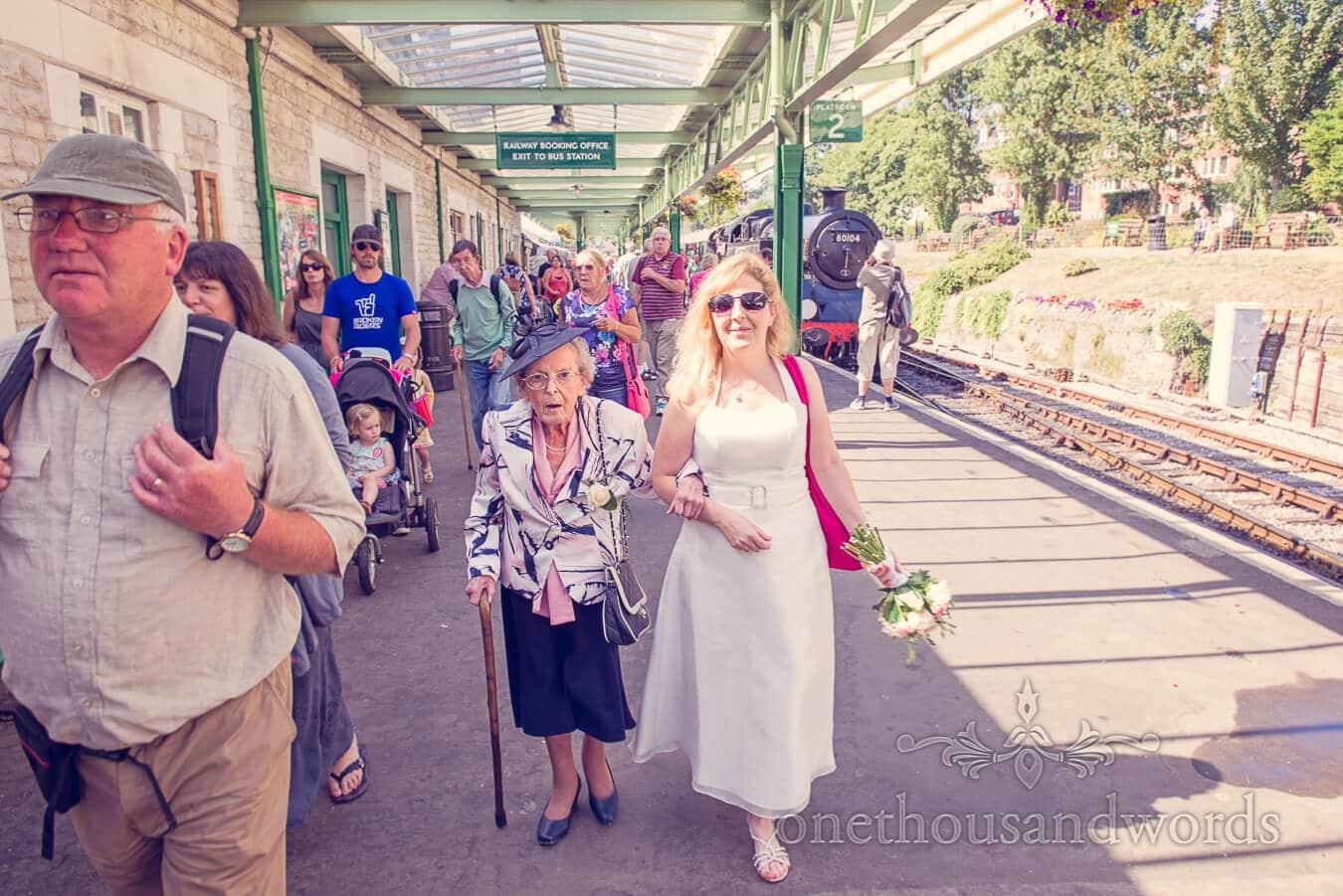 Bride walks grandmother on steam train station in Swanage