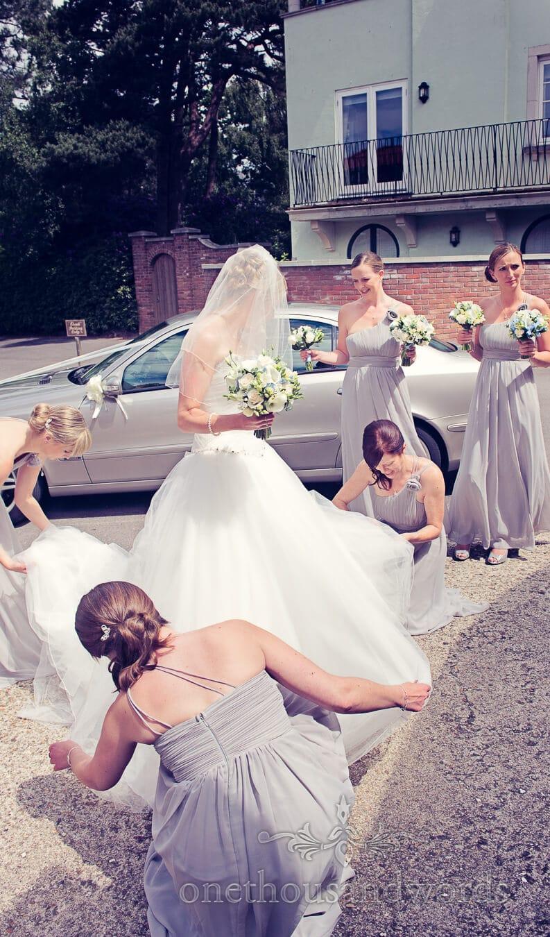 Bride has white wedding dress adjusted by bridesmaids Italian Villa Wedding