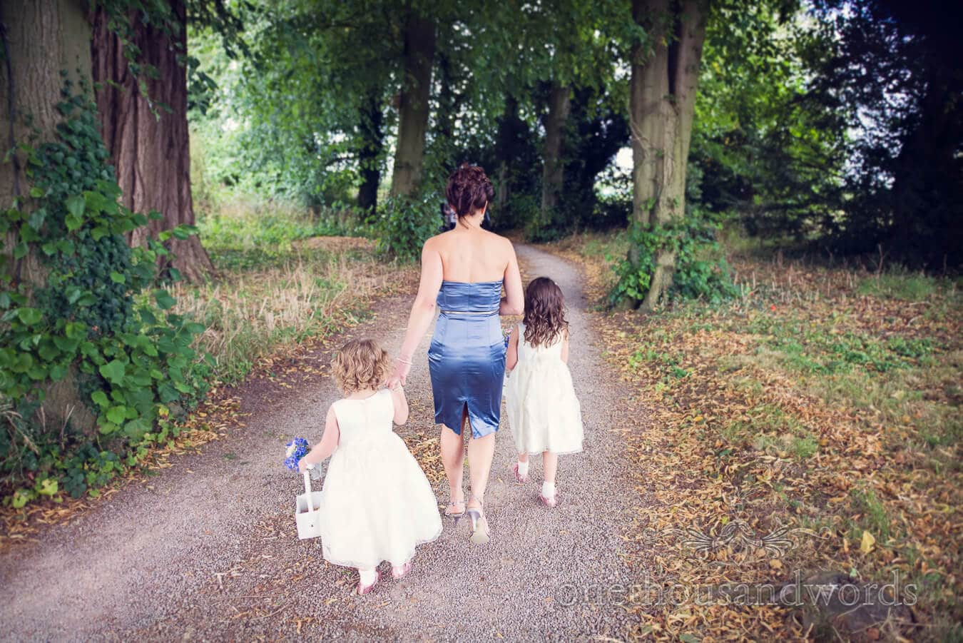 Bridesmaid and flower girls walk tree lined driveway at Countryside Wedding