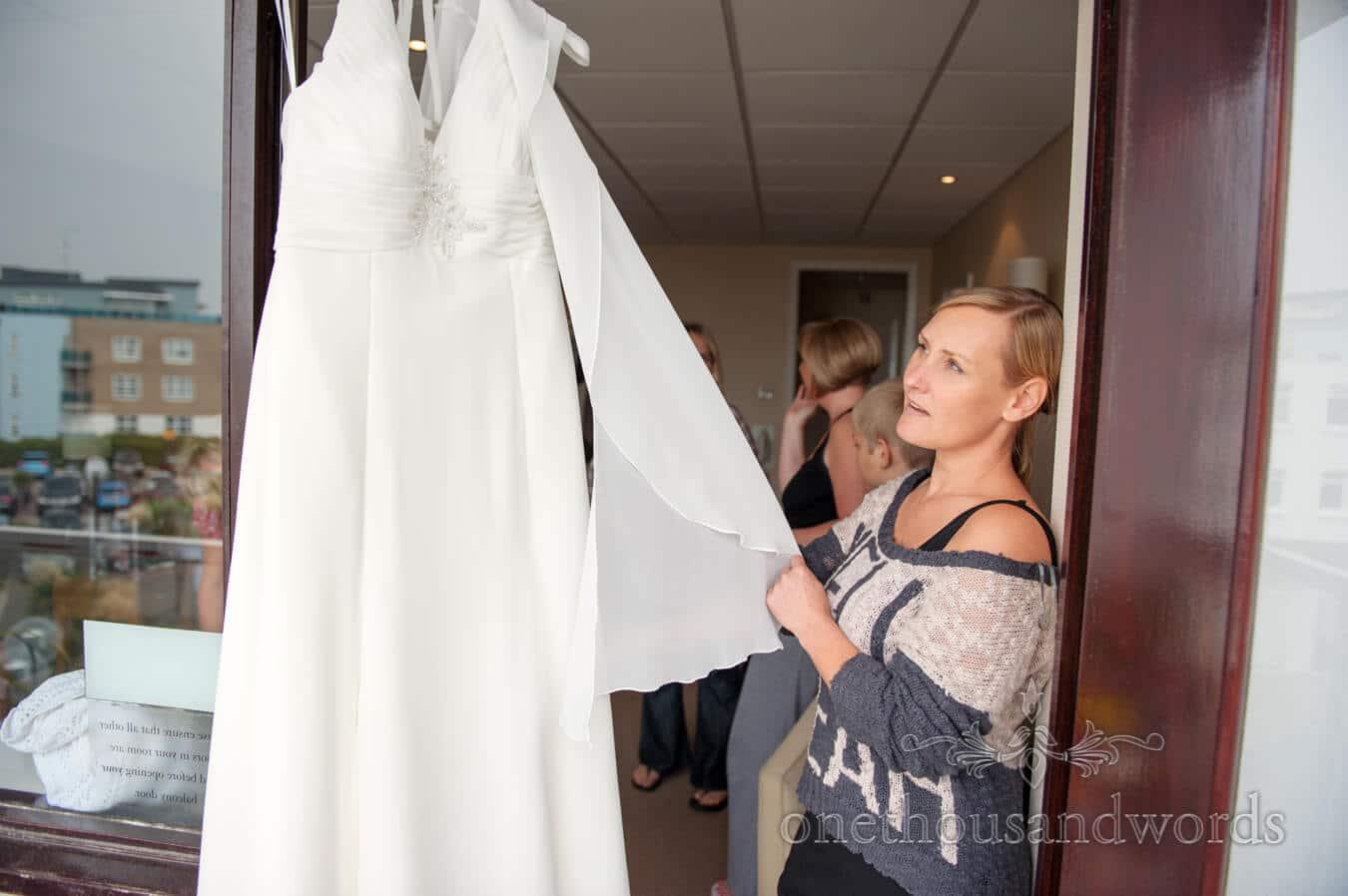 Bridesmaid looks at wedding dress at Sandbanks Hotel wedding morning