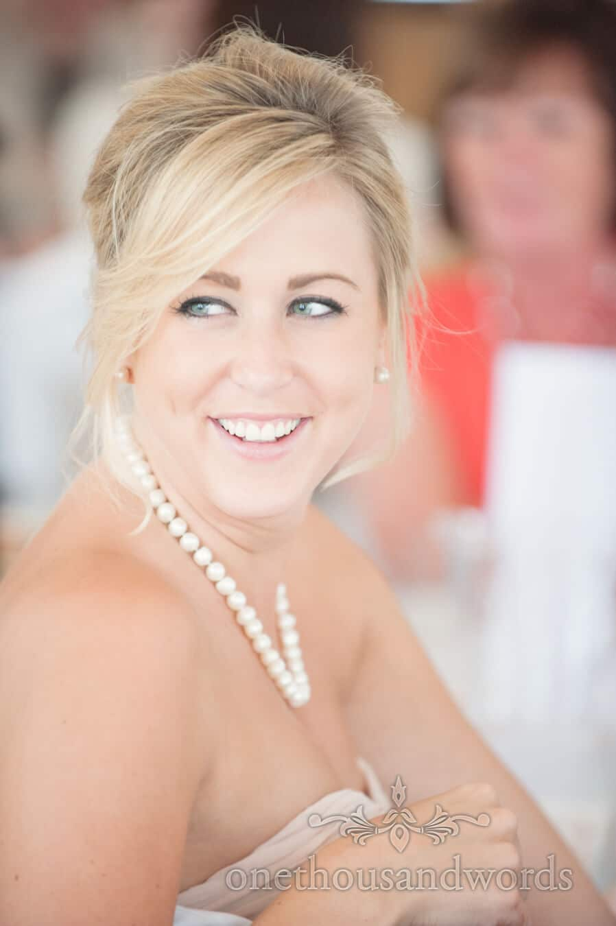 Blonde Bridesmaid with pearls portrait laughing at speeches