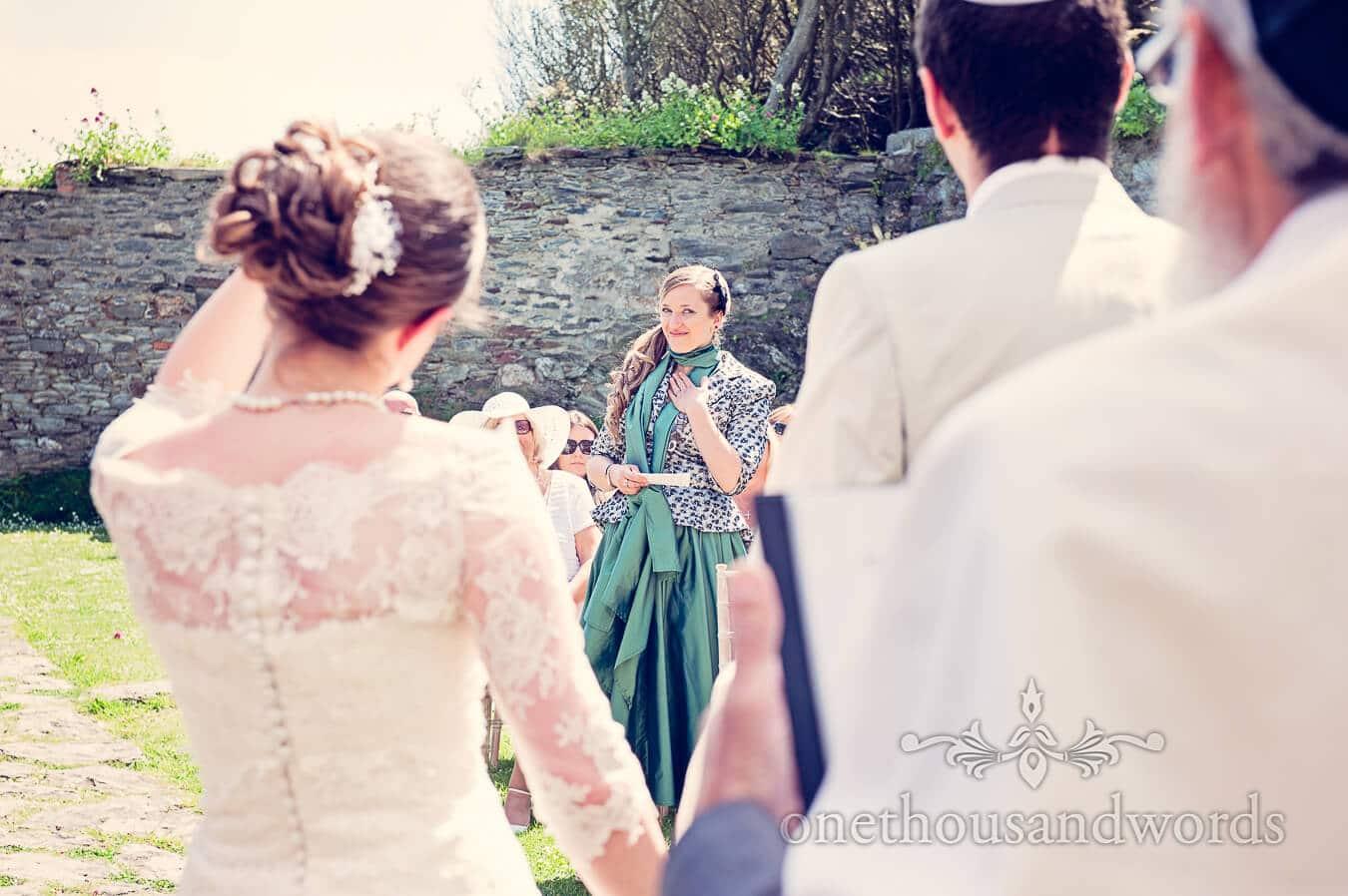 Bridesmaid reading at outdoor wedding ceremony in Cornwall