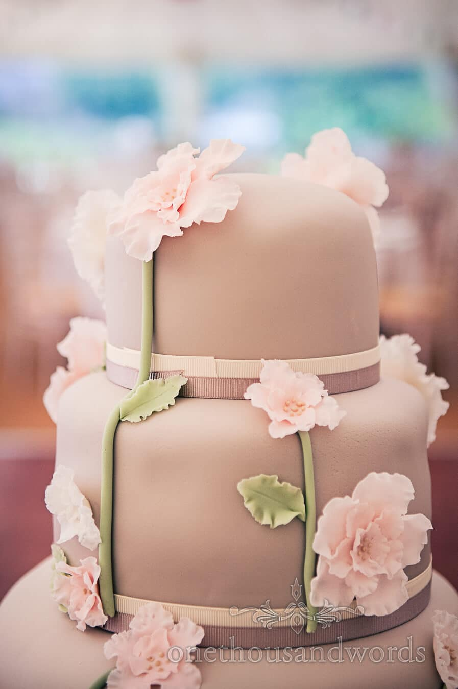 Brown wedding cake with pink flowers