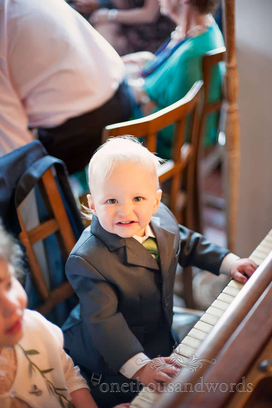 Child wedding guest plays piano at Prussia Cove
