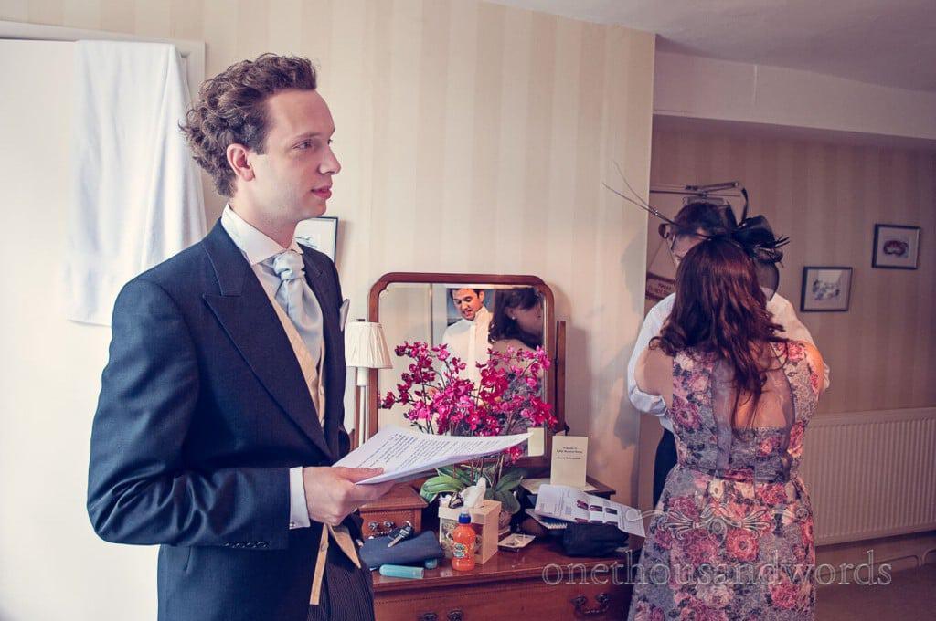 Best man practices wedding speech during groom preparation photographs
