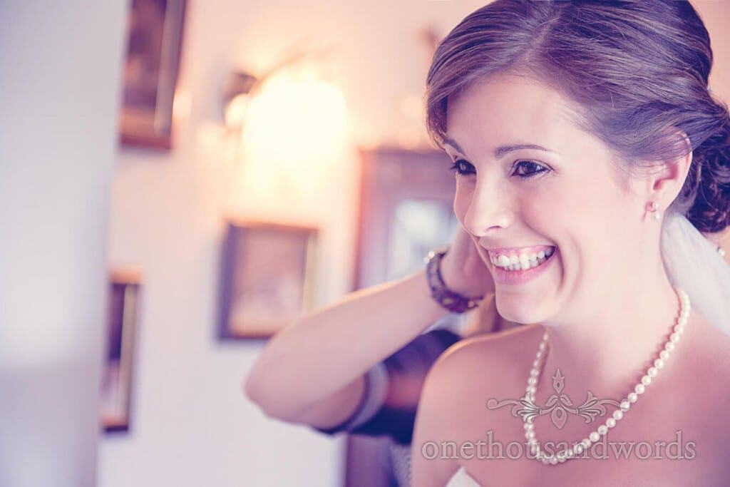 Happy bride with pearl necklace has wedding veil applied to hair