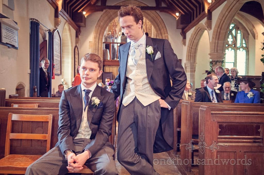 Groom and best man wait for bride in stone countryside church