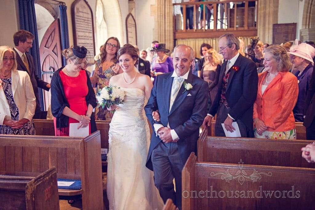 bride and her father walk down the aisle at church wedding ceremony