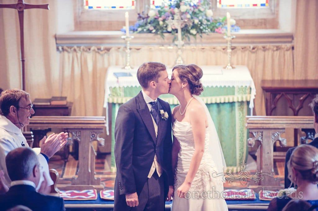 First kiss photograph with bride and groom church wedding ceremony