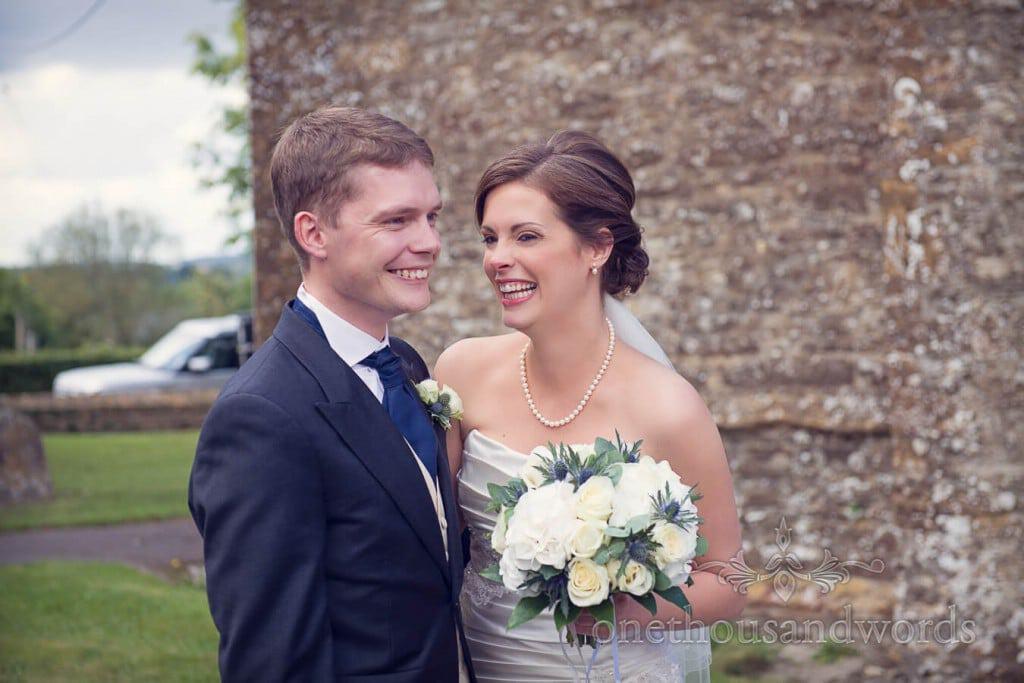 Bride adn groom outside countryside stone church on wedding day