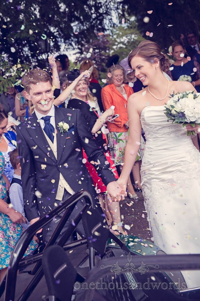 Wedding confetti with bride and groom outside countryside church