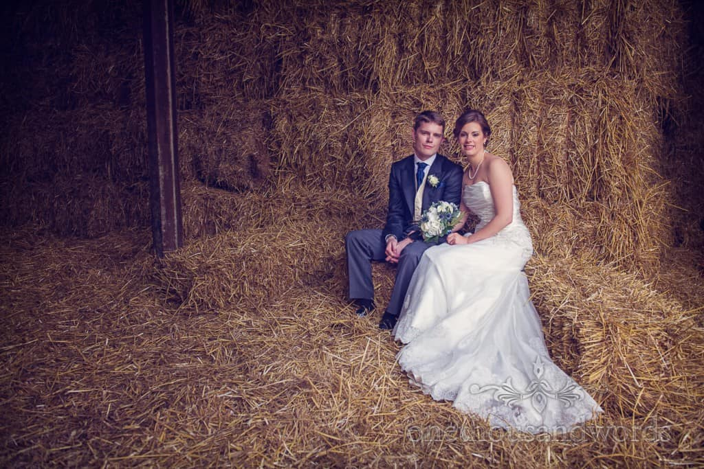 countryside themed wedding photos of bride and groom in staw bale barn
