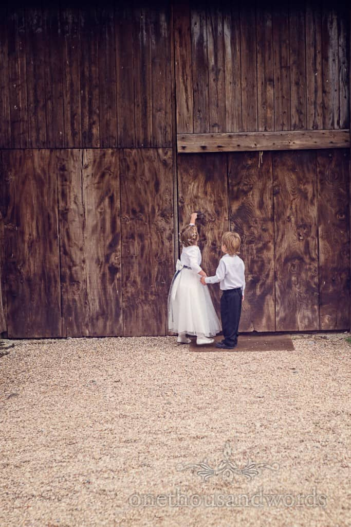 Flower girl opens barn door at countryside themed wedding