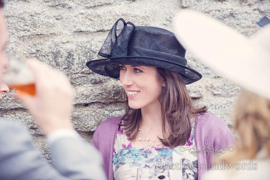 Beautiful wedding guest in blue wedding hat against barn stone wall
