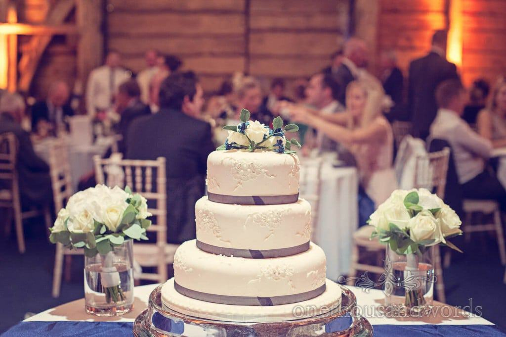 White three tier wedding cake with white wedding flowers in Dorset Barn venue