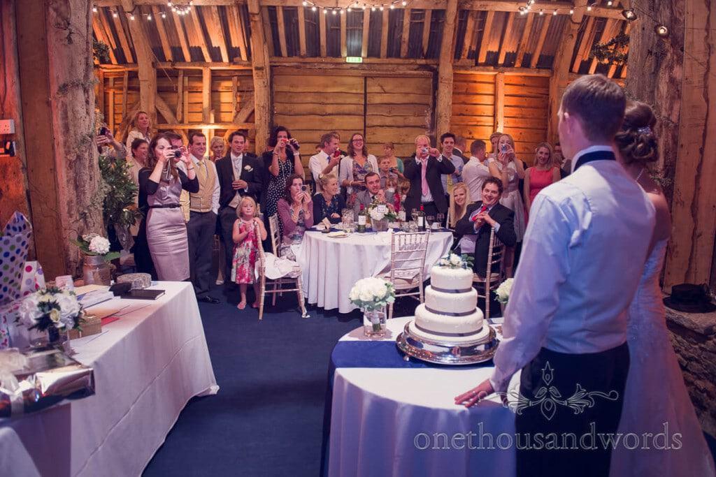 Bride and groom about to cut wedding cake at Stockbridge Farm Barn venue