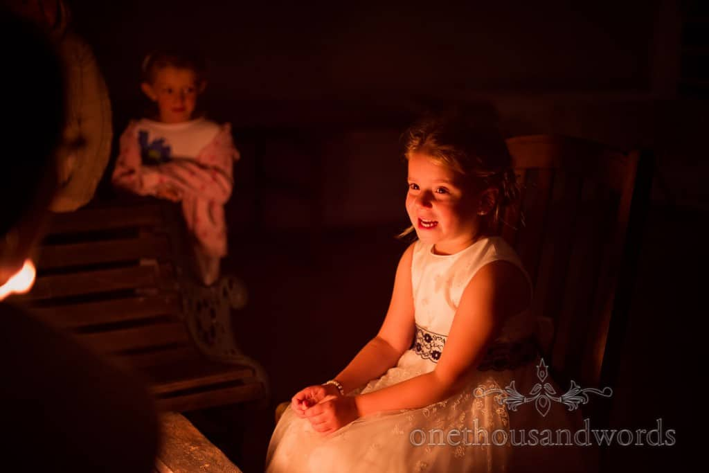 Flower girl sits by wedding firepit at countryside themed wedding