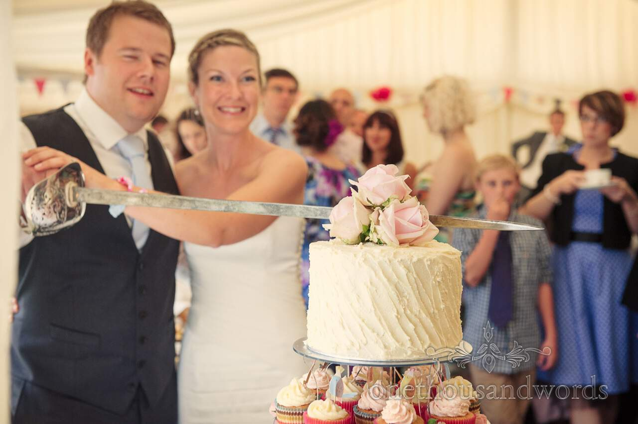 Cutting a wedding cake with a sword at Countryside marquee wedding photographs